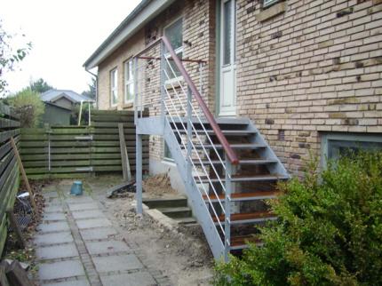 HOVEDTRAPPE INDGANG over kældertrappe. Mulighed for etablering af stabil vejrbestandig hovedtrappe over eksisterende beton-kældernedgangs-trappe. Renovering af gl. frostsprængt betontrappe. Tilpasset kunde design ønsker.. Gelænder-håndliste kan leveres som her med stålliste påmonteret håndliste af hårdttræ. Trappen kan etableres, tilpasses, over eksisterende beton-kældertrappe. Hovedtrappen`s repos monteres med stålbolte i husmur under hoveddør og trappen fastboltes på 2 punktfundamenter, et for bærende søjle ved kældertrappehjørne (kan dog udgøres af øverste eksisterende stabile kældermur) + punktfundament ved start af trappetrin.