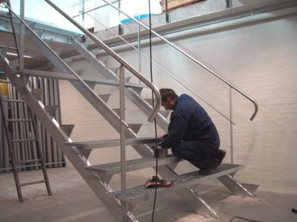Trappe udendørs / indendørs, lagertrappe i stål, varmgalvaniseret: Opsadlet ståltrappe m. gitterriste trin. Trappevanger 3 stk. af rør profilstål.